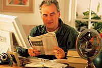 Mature man in front of computer reading newspaper