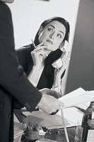 Business professional on telephone, colleague beside her