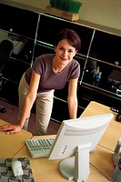 Woman standing behind computer desk, portrait