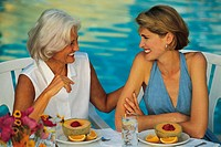 Women having breakfast at outside table, poolside