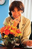 Woman on telephone with vase of flowers on desk and gift card in hand.