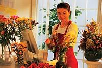 Female florist at register arranging flowers.