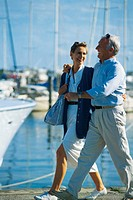 Mature couple walking by sailboats.