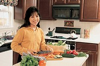 Woman in kitchen, making a salad, portrait