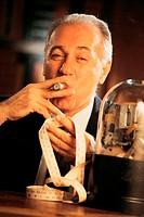 Mature businessman smoking cigar reading stock ticker
