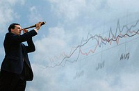 Businessman looking through telescope, stock market graph