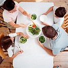 Family eating salad at table (thumbnail)