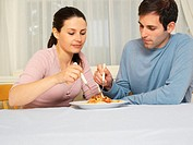 Couple sharing spaghetti bolognese