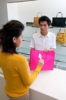 Woman buying handbag (thumbnail)