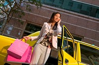 Woman leaving taxicab with shopping bags