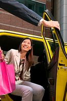 Female shopper leaving taxicab