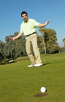 Man Stands on a Putting Green With His Arms Out in Disappointment, the Golf Ball at the Edge of the Hole