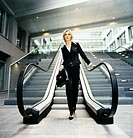 Smart Confident Businesswoman Carrying a Briefcase Descends an Escalator