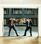 Two Rival Businessmen Stand Face to Face in an Office Lobby in Martial Arts Poses