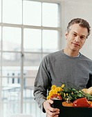Portrait of a Man Standing by a Window Holding a Box of Fresh Vegetables and Flowers