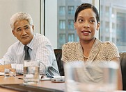 Businessman and Woman Sit Side-by-Side at a Conference Table