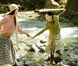 Young Woman Helping her Friend Across a Stoney River Bank