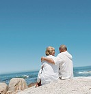 Rear View of a Senior Couple Sitting Side by Side on a Rock by the Sea