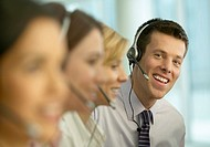 Portrait of a Businessman and Colleagues Wearing Headsets