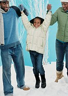 Parents Stand in the Snow, Lifting Their Young Daughter by the Arms and Swinging Her