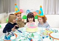 Four Children Gathered Round a Birthday Cake on a Table