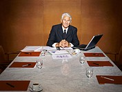 Portrait of a Senior CEO Sitting at the End of a Marble Table, in a Conference Room
