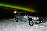 Aurora Borealis (northern Lights) over truck and the snow covered shore of Hudson Bay, Churchill, Manitoba, Canada.