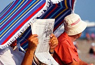 europe, uk, england, reading newspaper at the seaside