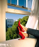 Woman relaxing on couch with red heels on. California. San Francisco. USA