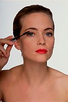Portrait of a young woman applying mascara (thumbnail)