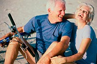 Senior couple standing with bicycles laughing