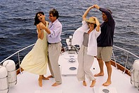 Two couples dancing on a boat