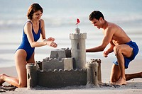 Couple building a sandcastle at the beach