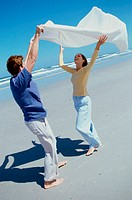 Young couple holding up a scarf on the beach