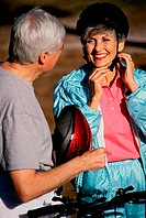Woman putting on a cycling helmet standing with a man