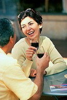 Couple sitting together toasting with red wine