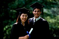 Portrait of a young woman and a young man wearing graduation outfits