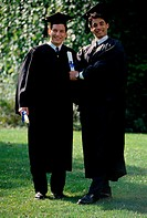 Portrait of two young men wearing graduation outfits holding diplomas (thumbnail)