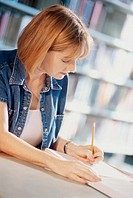 Side profile of a woman writing in a notebook with a pencil