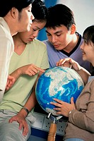 Teenage students pointing to a globe