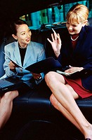 Two businesswomen discussing in a car