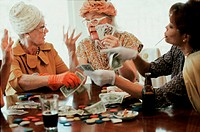 Three senior women playing cards