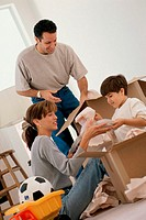 Young couple unpacking boxes with their son
