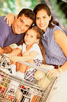 Portrait of a couple with their daughter sitting in a shopping cart