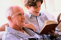 Teenage boy reading to an elderly man