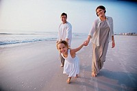 Couple with their daughter on the beach