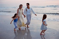 Father and mother walking with their two children at the beach