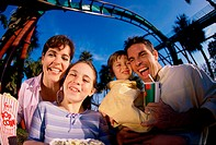 Portrait of parents and their two children in an amusement park