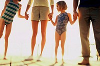 Low section view of a girl holding her parents hands standing at the beach