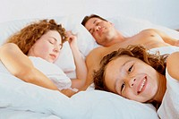 Close-up of a girl lying with her parents in bed